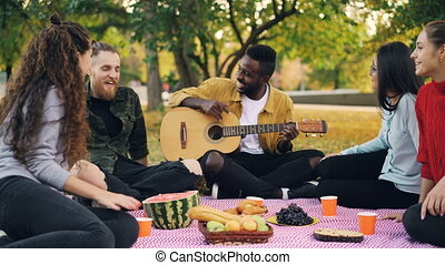 Cheerful African American man is playing the guitar for his friends sitting on blanket on picnic and enjoying warm autumn weekend. Leisure and music concept.