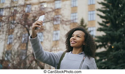 Cheerful african american student girl talking at video call...
