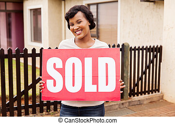 african american woman holding sold sign
