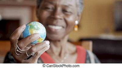 Cheerful African American woman looking at world map globe and smiling