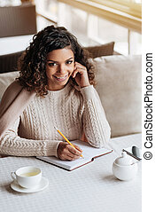 Cheerful African American woman making notes in the cafe