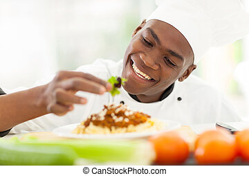 african chef decorating spaghetti