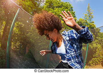 Cheerful African girl bouncing on the trampoline