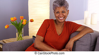 Cheerful African grandmother sitting on couch