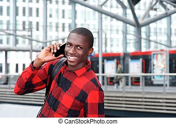 Cheerful african guy using cell phone at train station