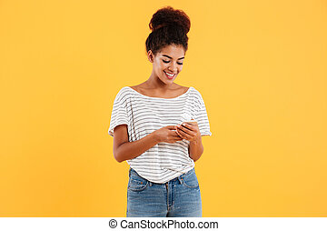 Cheerful african lady using and typing smartphone isolated
