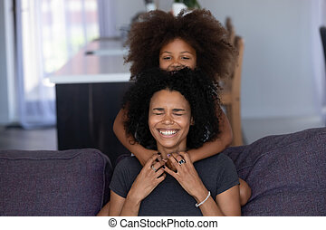 Cheerful african mom and kid daughter laughing embracing at home