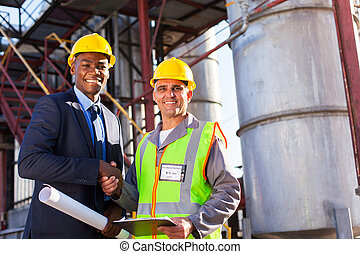 cheerful african refinery manager handshaking with senior worker in front of fuel-tanks