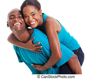 african woman enjoying piggyback ride on boyfriends back -...