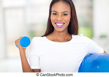 african woman exercising with dumbbell