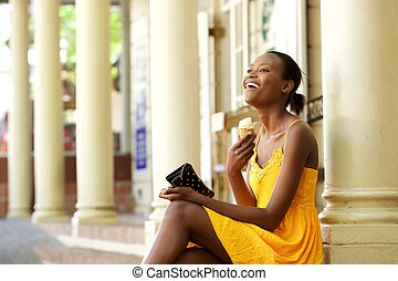 Cheerful african woman sitting outdoors with ice cream
