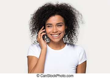 Cheerful african woman talking on mobile phone isolated on grey