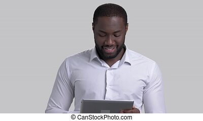 Cheerful afro-american businessman using electronic tablet.