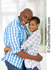 afro american couple hugging at home