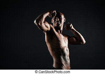 Cheerful afro american sports man showing his biceps