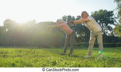 Cheerful aged coupe enjoying warm up exercises outdoors - Do...