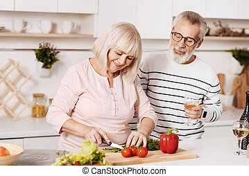 Cheerful aged couple cooking in the kitchen