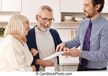 Cheerful aged couple owners meeting real estate agent at home