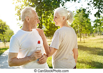 Cheerful aged couple resting after sport exercises