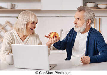 Cheerful aged couple spending weekend at home