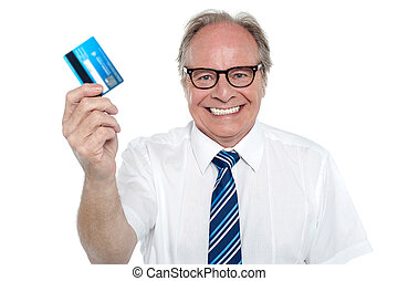 Cheerful aged employer holding up a cash card and smiling at...