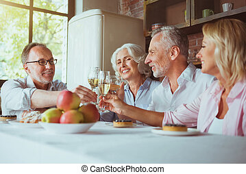 Cheerful aged frineds drinking champagne at home