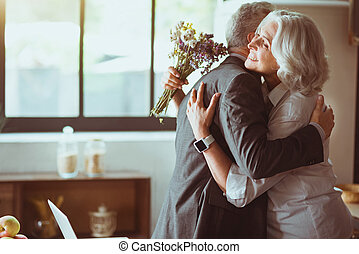 Cheerful aged loving couple embracing at home