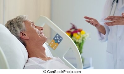 Cheerful aged male patient talking with his professional...