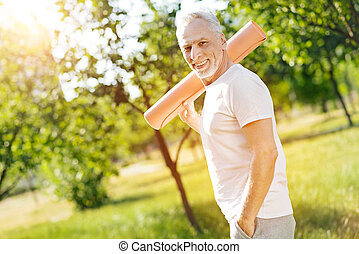 Cheerful aged man holding roll mat on the shoulder