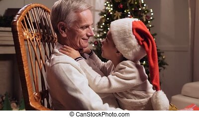 Cheerful aged man playing with his grandfather in the rocking chair
