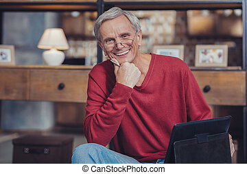 Cheerful aged man smiling while relaxing with his tablet