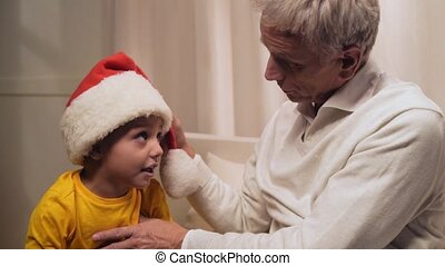 Cheerful aged man wearing Christmas hat on his grandson
