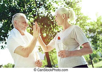 Cheerful aged woman greeting her husband