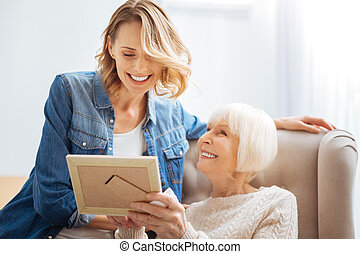 Cheerful aged woman laughing and showing a funny photo to her granddaughter