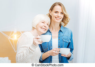 Cheerful aged woman leaning to her granddaughter while standing with a cup
