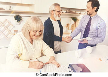 Cheerful aged woman signing papers - Come to agreement....