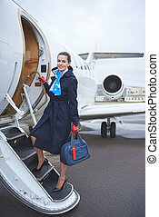Cheerful air-hostess entering airplane with bag