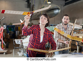 Cheerful aircraft enthusiasts with airplane models