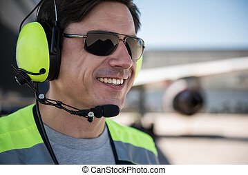 Cheerful airport worker in sunglasses and headset