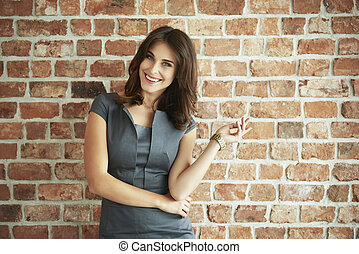 Cheerful and attractive woman on brick wall