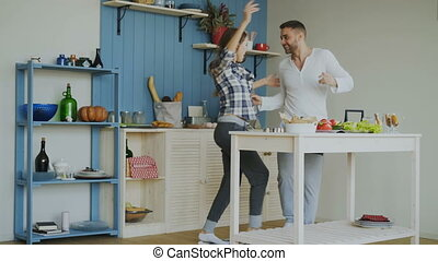 Cheerful and attractive young couple in love dancing together rocknroll dance in the kitchen at home on holidays