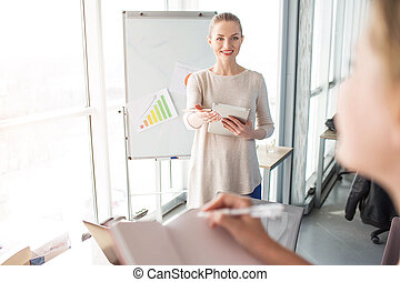 Cheerful and happy speaker is standin near flipchart with diagrams. She is waiting while the girl with notebook will answer to her question.