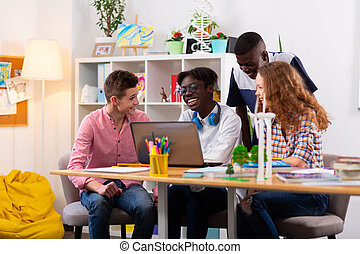 Four teenagers feeling cheerful and positive while studying together