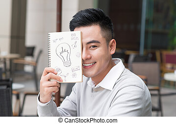 Cheerful asian businessman showing creative idea documents