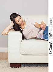 Cheerful asian girl lying on the couch reading a magazine