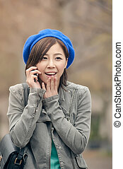 Cheerful Asian lady talking on cellphone at street in the park,