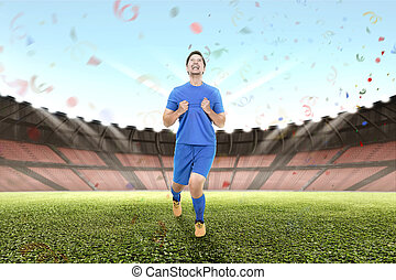 Cheerful asian male soccer player celebrate