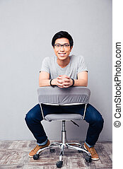 Cheerful asian man sitting on the chair