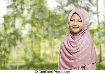 Cheerful asian muslim woman wearing hijab standing