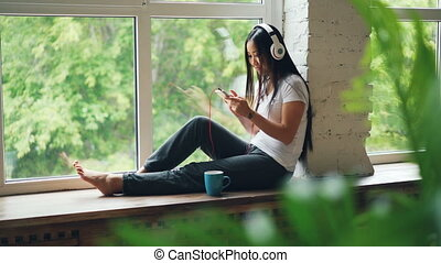 Cheerful Asian woman is listening to favourite song in...